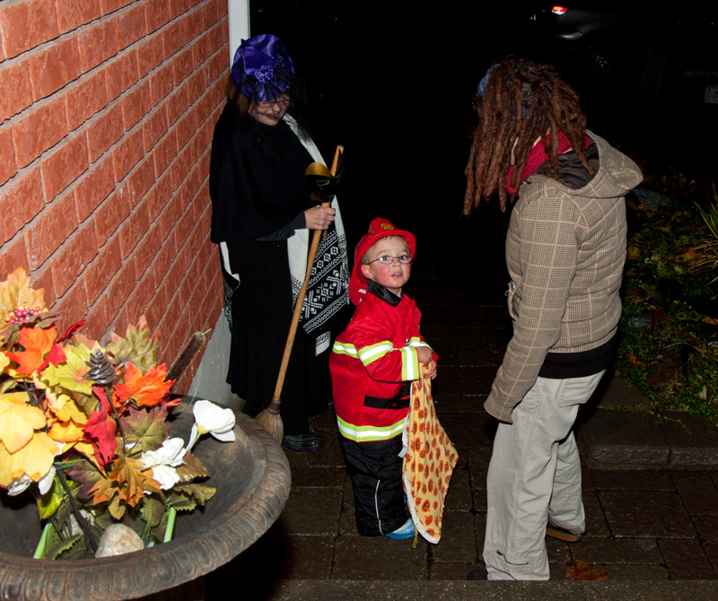 A toddler dressed up as a fireman at halloween, trick or treating with him mom and grandmom.