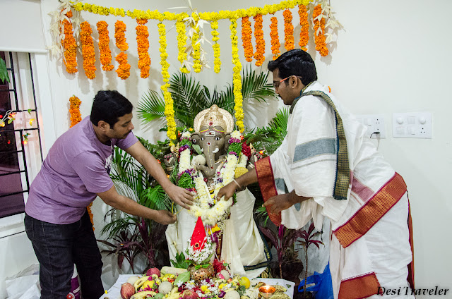 putting garland on eco friendly ganpati idol with priest