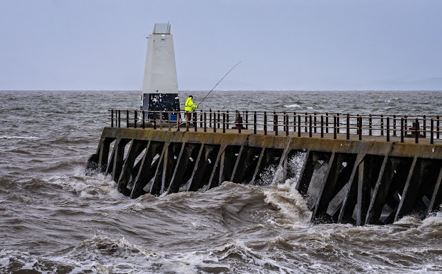 Photo of a fisherman braving windy conditions on Maryport pier