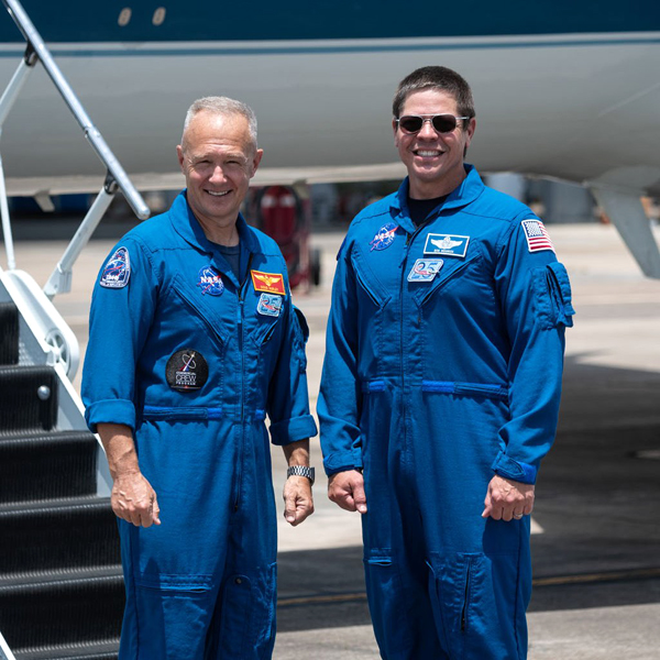 NASA astronauts Douglas Hurley and Robert Behnken pose for the cameras at the Launch and Landing Facility after arriving at the Kennedy Space Center in Florida...on May 20, 2020.