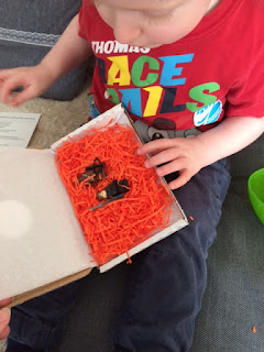 A little boy opening a box with mini figures inside
