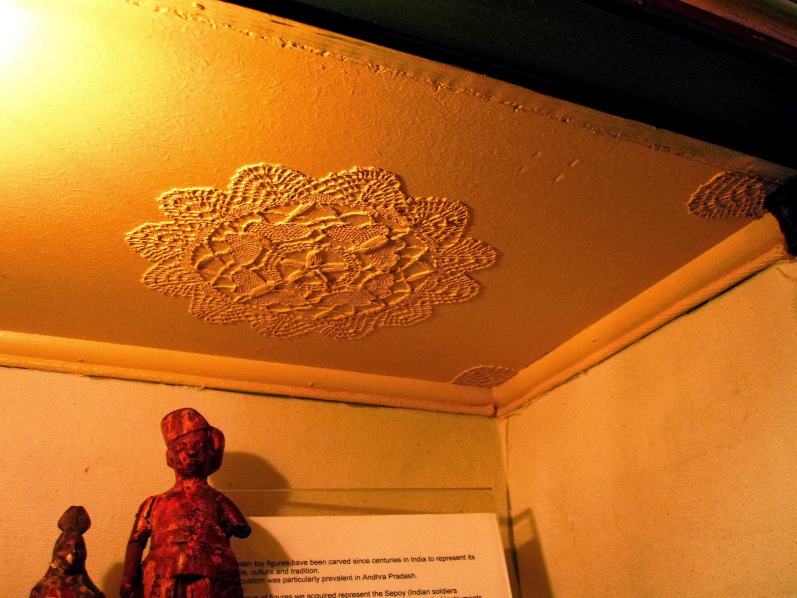 Ceiling of a room in the dolls house display cabinet, showing doileys stuck to it to replicate plaster moldings