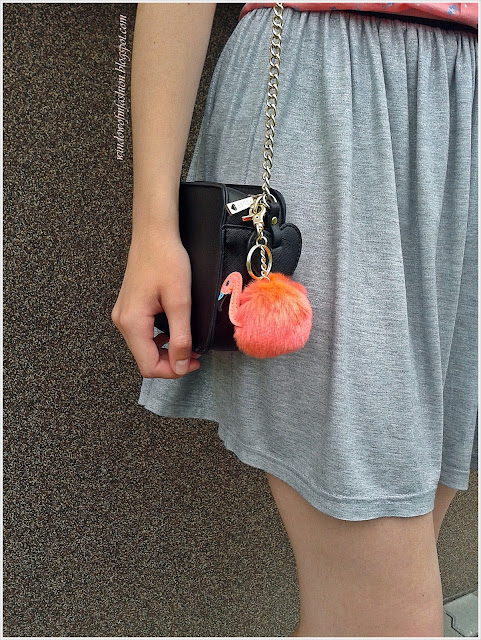 Breloczek z flamingiem, czarna torebka na złotym łańcuszku, szaro-srebrna spódniczka