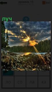 С неба едва пробивается через облака луч солнца на эемлю