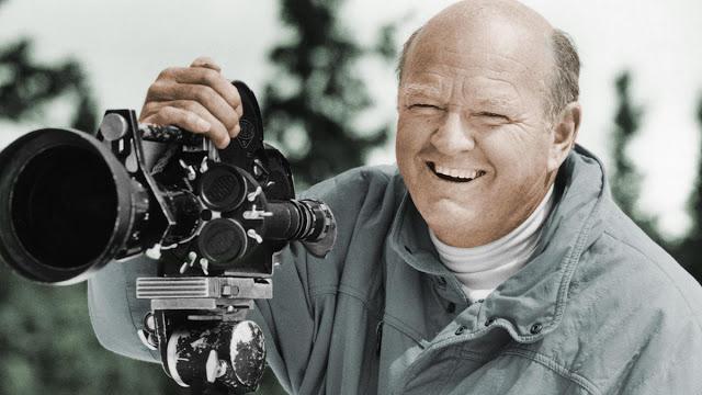 warren miller smiling as he films