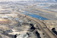 An open pit where tar sands are mined, with a heavy hauler truck that is used to transport oil sand to processing facilities. (Credit: Environment Canada) Click to Enlarge.