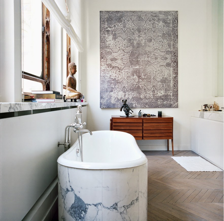 tub wrapped up in white veined marble on chevron floor