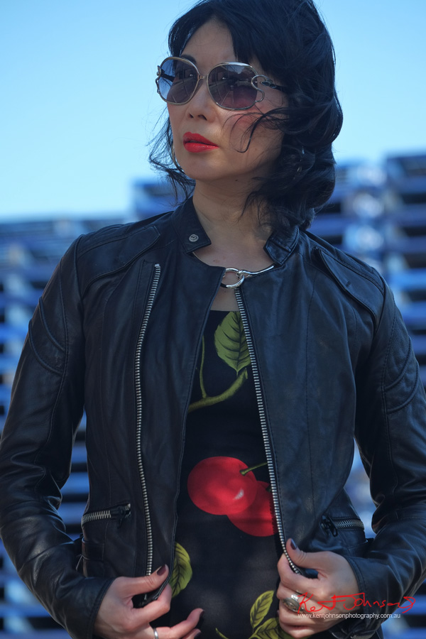 Mid shot - Industrial zone photoshoot with an empahasis on blue red and black. Marrickville Sydney, Cherry Dress, Leather Jacket, Sunglasses, with Fashion Blogger vivalaViv. Photographed by Kent Johnson.