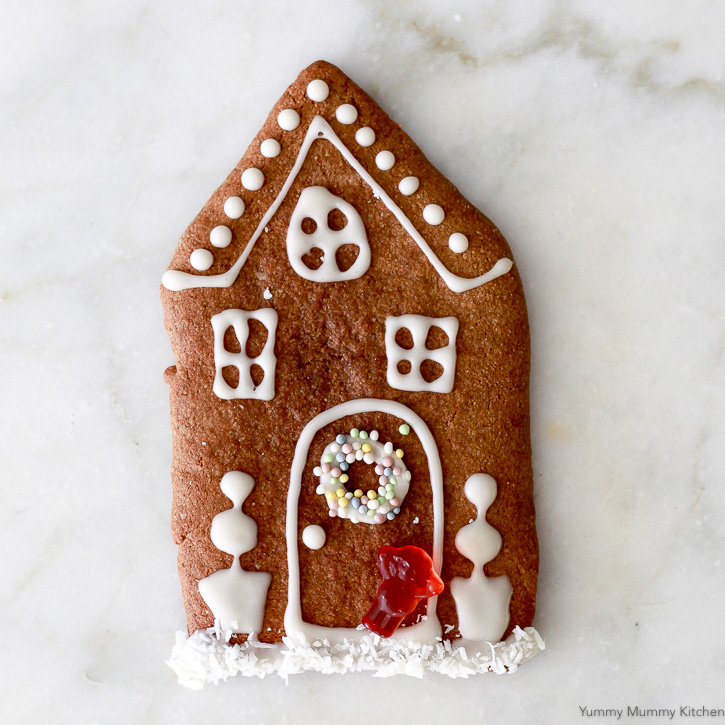 Beautiful decorated gingerbread house cookie made with healthier ingredients like almond flour and maple syrup.