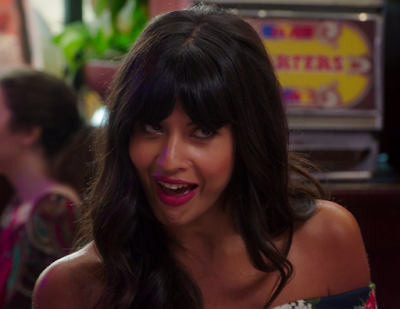Tahani looking up at Trevor in a conspiratory way with a big grin on her face