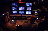 Ekran ve cihazların bulunduğu karanlık bir reji odasında oturan ve yayını izleyen yapımcı ve yönetmenler