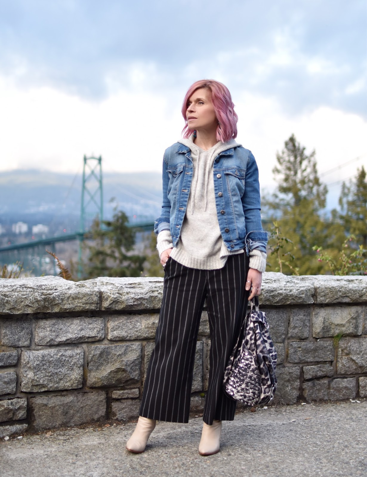 Monika Faulkner outfit inspiration - styling striped cropped trousers with a hoodie sweater, denim jacket, and ivory booties