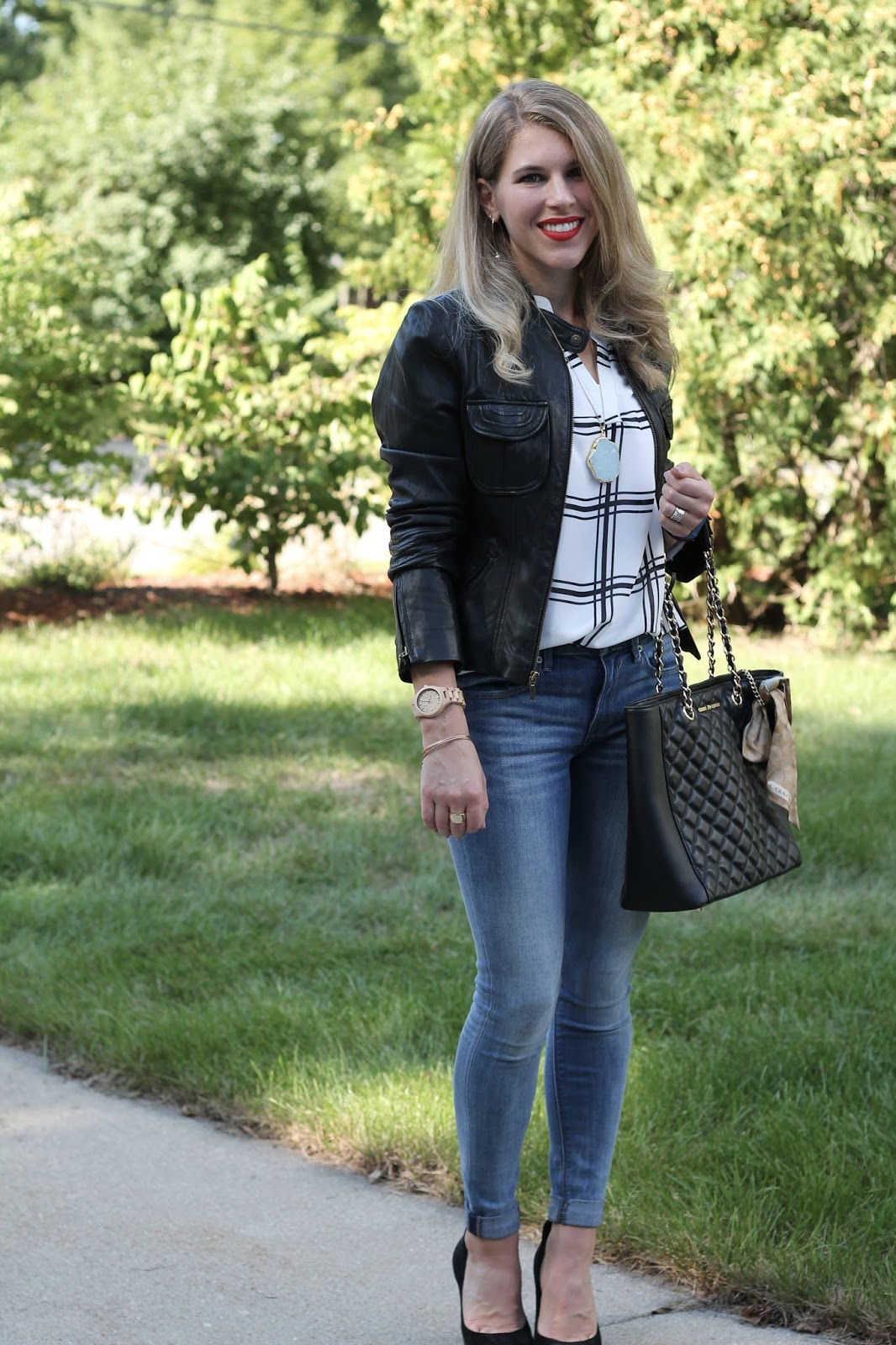 white and black windowpane blouse, jeans, black heels. Greg Michaels tote, black moto jacket, turquoise necklace and earrings