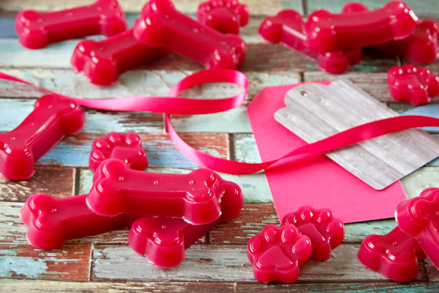 Bright pink gelatin gummy dog treats shaped like bones and paws