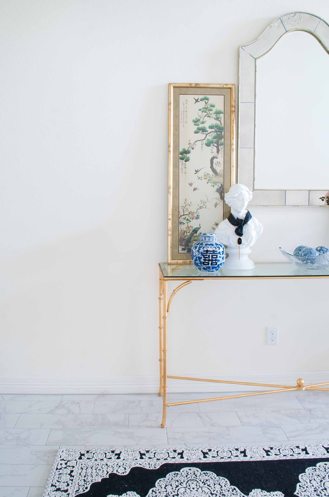 Gold console table with chinoiserie decor and black and white touches in a foyer.