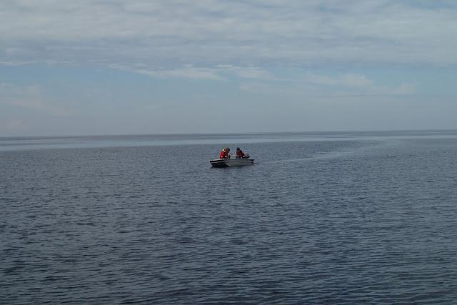 Pikkuinen alumiinivene, jossa kyydissä kaksi ihmistä.