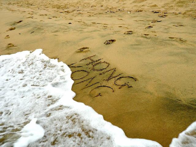 Hong Kong writing in the sand being washed away on Cheung Sha beach, Lantau Island, Hong Kong