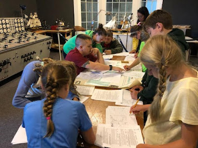 Students around a table with worksheets and other papers