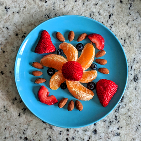 image of a carefully arranged fruit-and-nut plate, featuring orange slices, strawberries, blueberries, and almonds