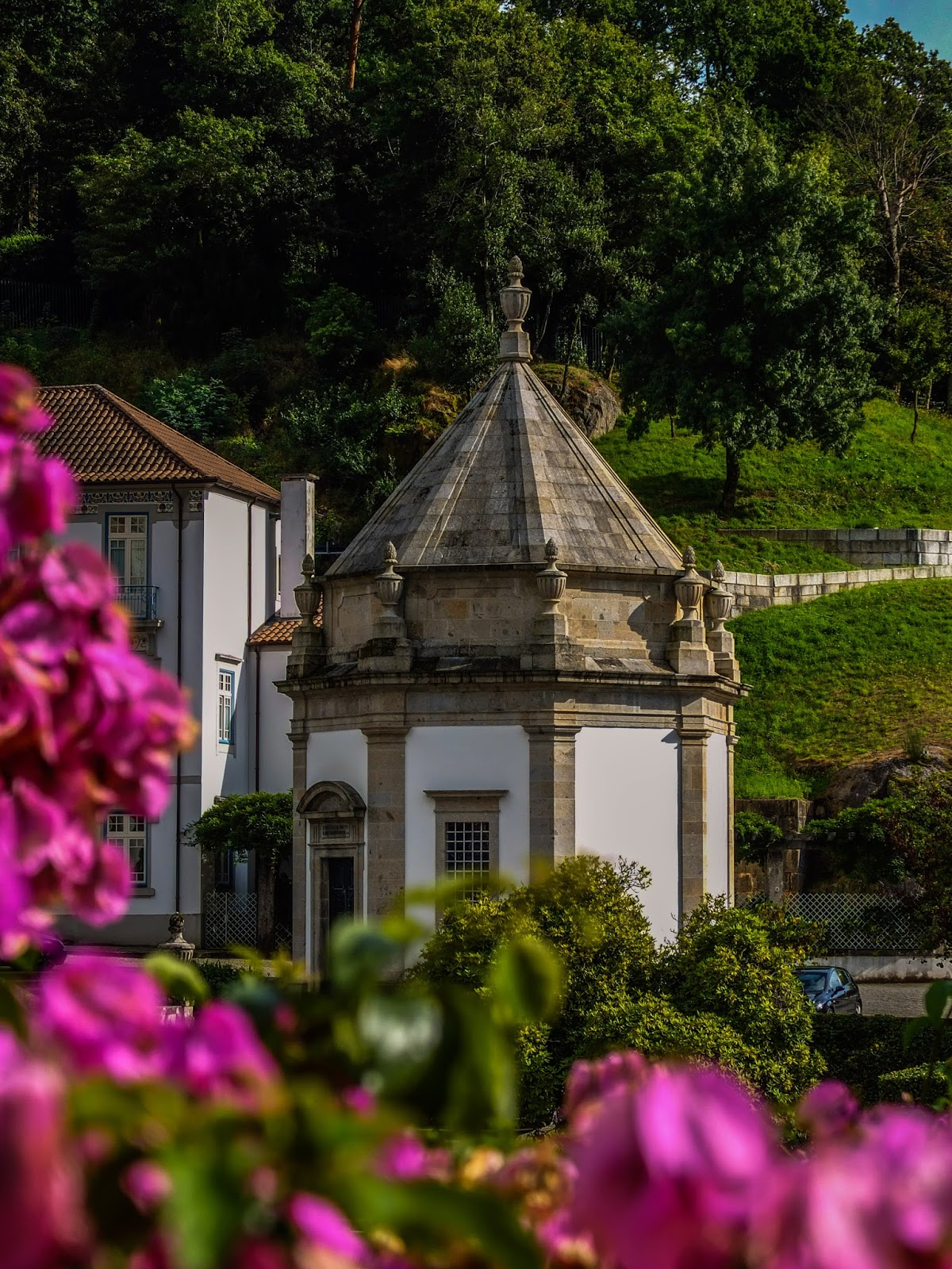 A chapel in the Sanctuary of Bom Jesus in Braga with pink flowers surrounding the frame.