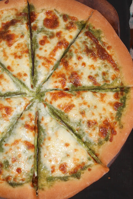 Garlic scape and olive oil cheese pizza cut into pieces.