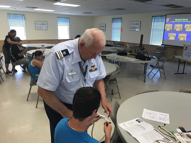 Auxiliarist John Fisher helps a student perfect his knot skills through one on one instruction.