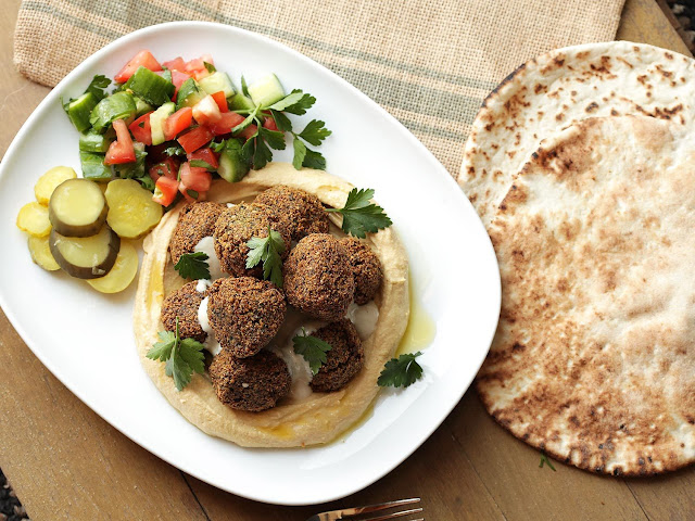 Falafel over hummus with salad pickles in a serving dish and pita bread