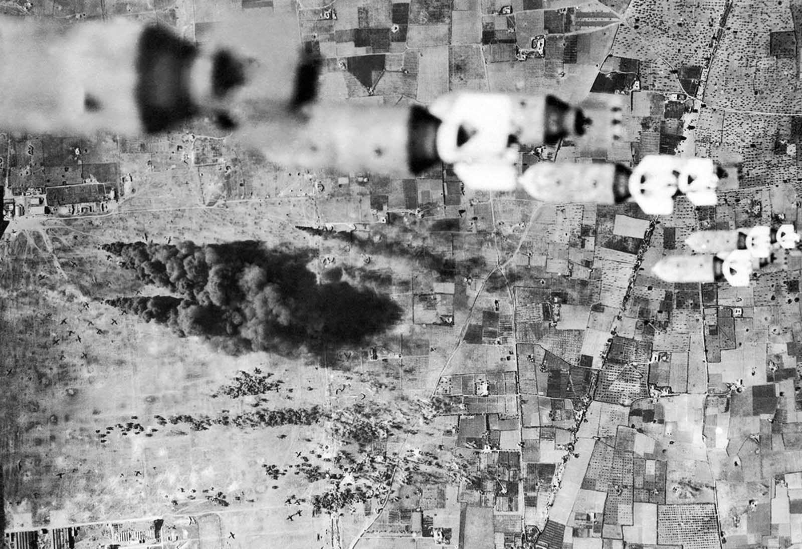 B-17 bombers, of the U.S. Army's Twelfth Air force, dropped fragmentation bombs on the important El Aouina airdrome at Tunis, Tunisia, and covered the airdrome and field completely. On the field below enemy planes can be seen burning, on February 14, 1943.