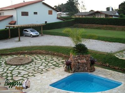Construção do campo de futebol em sítio em Atibaia-SP com o gramado com grama esmeralda, o estacionamento com o piso de pedrisco com o pergolado de madeira, os murinhos de pedra ornamental, construção da piscina, a cascata de pedra e os pisos de pedra São Tomé.