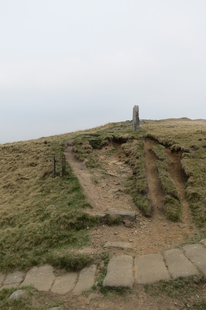 A stone laid path cuts across the foreground and a path of bare earth leads uphill at 90 degrees from it. A stone post acts as a waymarker for the second path.