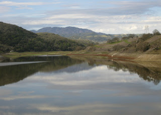 Cloudy skies and hills reflected on the surface of the Chesbro Reservoir, Morgan Hill, California