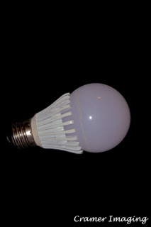 Photograph of a single LED light bulb on its side on a black background by Cramer Imaging