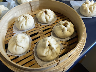 Five pork buns on pieces of baking paper in a large bamboo steamer