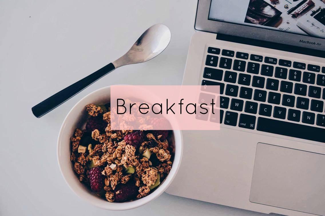Bovenaanzicht van een kom granola en fruit met daarnaast een lepel en een laptop.