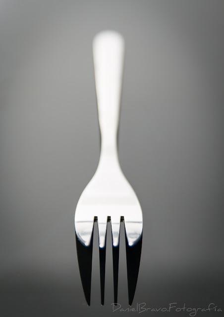 Tenedor plateado, sobre fondo negro. Imagen minimalista.