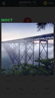 Длинный и высокий мост скрывается тумане вместе с пролетами