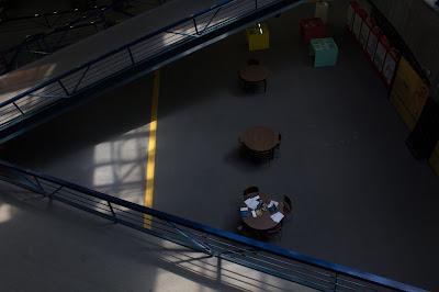 Duas escadas se cruzam e três mesas ficam entre elas formando um triângulo