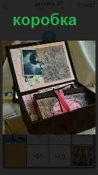 открытая коробка в которой лежат старые фотографии и другие вещи
