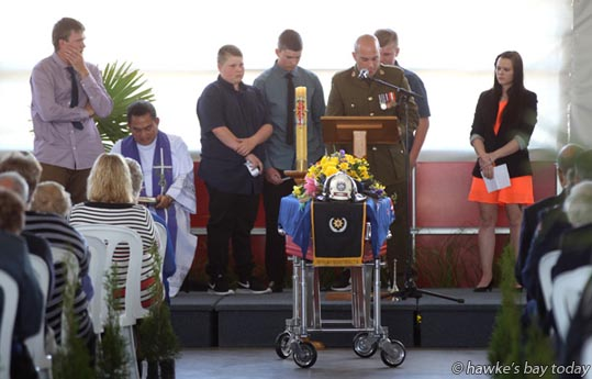 Family members speak at the funeral of Kevin Adie, a firefighter of 34 years and a community worker, at the Hastings Fire Station, Hastings. At the end of the service he was carried away on a vintage trailer pump and Dennis Fire engine for a circuit of the Hawke's Bay Hospital block. photograph