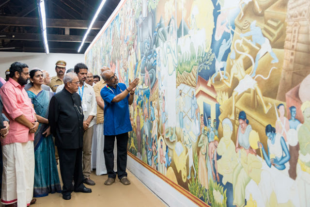 Artist P K Sadanandan Master explaining his mural work 'Parayi Petta Panthiru Kulam' to President Pranab Mukkherjee at Aspinwall House.  Minister for Tourism Kadakampally Surendran, Kochi Corporation Mayor Saumini Jain and Kochi Biennale 2016 curator Sudarshan Shetty are seen along.