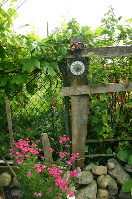 Garden decor with found objects: clock and goggles
