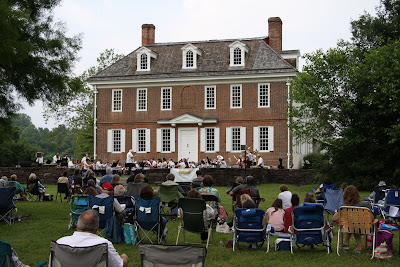 Hope Lodge mansion with people in chairs on lawn listening to concert