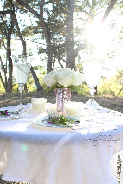 Outdoor table setting with flowers and sunset in background