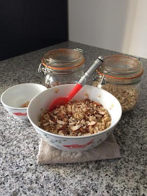 Un bol de flocons d'avoines aux amandes accompagné de deux bocaux en verre avec les ingrédients amande et flocons d'avoine sur plan de travail en granit