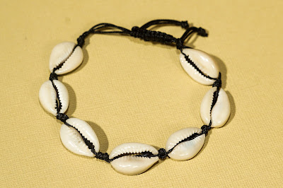White seashell bracelet on knotted black cord on cream background