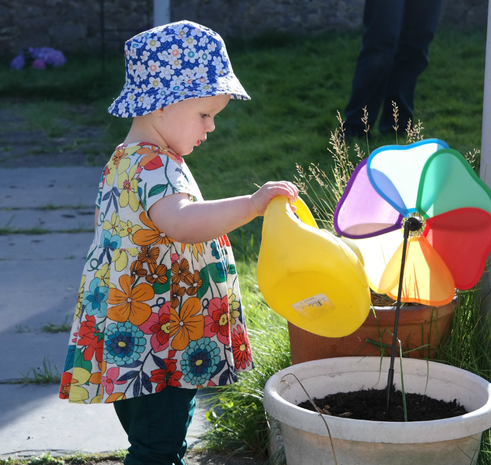 Family Garden in Summer: Toddler Watering Plants