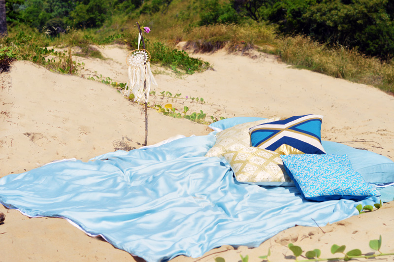 ettitude organic baby blue lyocell bamboo sheets used in boho beach set up on tropical beach