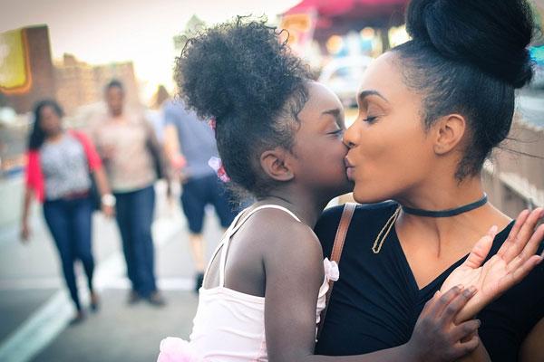 mulher beijando a filha no colo