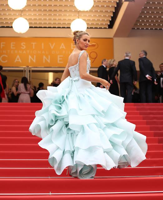 Blake subindo as escadas olhando para trás com seu vestido de saia bufante lembra a Cindela no baile