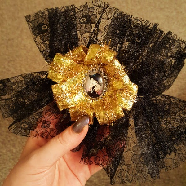 hand holding finished black lace ankle cuff with gold ribbon rosette trim